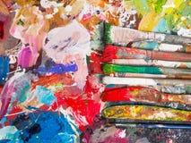Spazzola e tavolozza luminosa della petrolio-pittura per fondo Immagine Stock