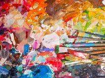 Spazzola e tavolozza luminosa della petrolio-pittura per fondo Fotografie Stock