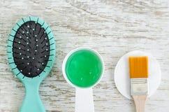 Spazzola per capelli e piccolo mestolo con il condizionatore verde della maschera dei capelli del gel con lo spirulina, l'aloe ve Fotografia Stock