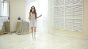 Spazzola per i capelli sveglia della tenuta della bambina come un microfono, un canto e dancing a casa video d archivio