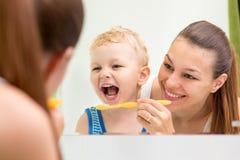 Spazzolatura di denti d'istruzione del bambino della madre Fotografia Stock