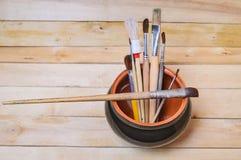 Spazzole artistiche in un vaso di argilla fotografia stock libera da diritti