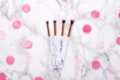 Spazzole cosmetiche con le decorazioni rosa su un fondo di marmo immagini stock