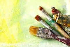 Spazzole degli artisti dell'annata e tubi della pittura su un fondo artistico astratto Fotografie Stock Libere da Diritti