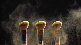 Spazzole del cosmetico con polvere cosmetica dorata su fondo nero video d archivio