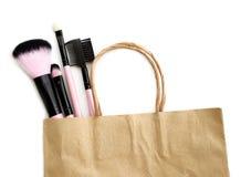 Spazzole del cosmetico di acquisto nell'isolato del sacco di carta su bianco Immagini Stock Libere da Diritti