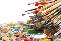 Spazzole di arte sulla tavolozza dell'artista Fotografia Stock