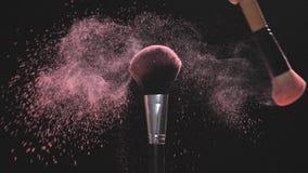 Spazzole di trucco con polvere rosa su un fondo nero al rallentatore archivi video