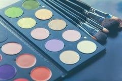 Spazzole di trucco e ombretti di trucco sullo scrittorio Fotografie Stock