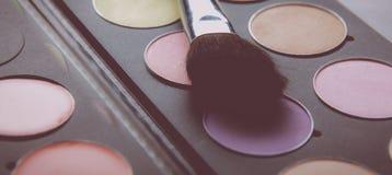 Spazzole di trucco e ombretti di trucco sullo scrittorio Fotografia Stock
