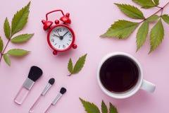Spazzole di trucco, una tazza di caffè ed orologio su fondo pastello rosa Concetto di bellezza Fotografia Stock