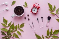 Spazzole di trucco, una tazza di caffè ed orologio su fondo pastello rosa Concetto di bellezza Fotografie Stock