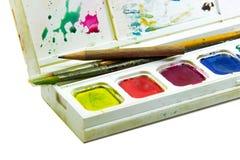 Spazzole e matita in scatola dei colori dell'acqua su fondo bianco Immagine Stock Libera da Diritti
