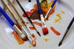 Spazzole e pitture su un piatto Fotografie Stock