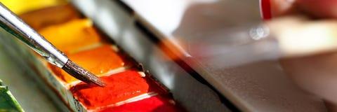Spazzole femminili dell'acquerello della tenuta due della mano dell'artista Immagine Stock Libera da Diritti