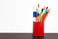 Spazzole, matite ed indicatore di lavagna in una tazza rossa Immagini Stock