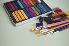 Spazzole multicolori, acquerelli e pastelli su un fondo verde Fotografia Stock Libera da Diritti