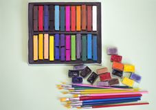 Spazzole multicolori, acquerelli e pastelli su un fondo verde Fotografie Stock Libere da Diritti