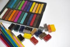 Spazzole multicolori, acquerelli e pastelli su un fondo verde Fotografia Stock