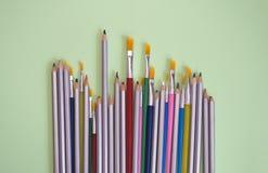Spazzole multicolori e matite su un fondo verde Fotografie Stock
