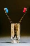Spazzole rosse e blu dei denti in un vetro su fondo nero Immagine Stock Libera da Diritti