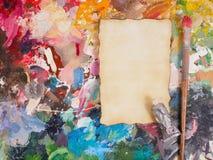 Spazzoli ed incarti sulla tavolozza della petrolio-pittura per fondo Fotografie Stock