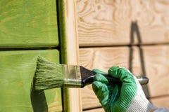 Spazzoli il primo piano del pittore che dipinge la parete di legno nel verde Fotografia Stock