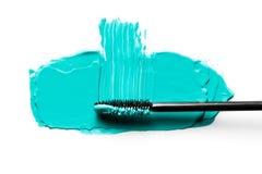 Spazzoli per i cigli su una sbavatura di mascara azzurrata Isolato su priorità bassa bianca immagine stock