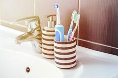 Spazzolini da denti elettrici e manuali nell'interno del bagno fotografie stock
