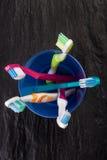 Spazzolini da denti in un vetro di plastica blu su fondo di pietra nero Fotografia Stock