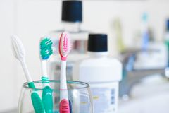 Spazzolini da denti in vetro sulla tavola in bagno Immagine Stock