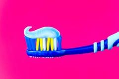 Spazzolino da denti blu con dentifricio in pasta blu su un fondo cremisi Immagini Stock