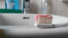 Spazzolino da denti con dentifricio in pasta su un lavandino Immagine Stock Libera da Diritti