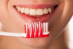 Spazzolino da denti della tenuta della donna davanti ai denti che promuovono il hygie della bocca Fotografia Stock
