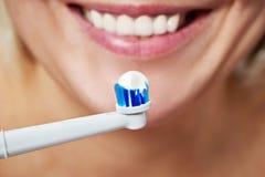 Spazzolino da denti elettrico di spazzolatura dei denti della donna con dentifricio in pasta fotografie stock