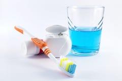 Spazzolino da denti, filo per i denti, dentifricio in pasta e colluttorio su fondo bianco Immagine Stock Libera da Diritti