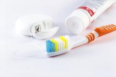 Spazzolino da denti, filo per i denti e dentifricio in pasta su fondo bianco Immagine Stock