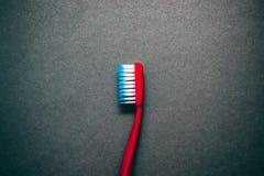 Spazzolino da denti rosso su fondo lateralmente immagine stock libera da diritti