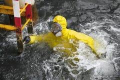 Spécialiste en eau de mer essayant d'atteindre l'échelle pour sauver sa vie Photo libre de droits