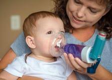 Spädbarn som får andningbehandling från moder Arkivbild