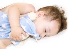 Spädbarnet behandla som ett barn att sova för pojke Behandla som ett barn att sova med hennes nallebjörn, nya mjuka fokus för fam Royaltyfri Foto