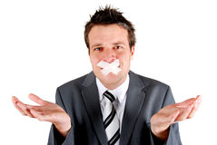 Speach denied. Man with tape over his mouth in a gesturing pose of speechlessness Stock Photos