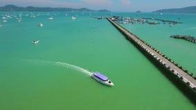 Speadboat do cruzeiro com os turistas que navegam na água do mar azul ao cais A antena de HD segue o tiro Phuket, Tailândia filme