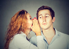 Speak in the ear. Woman whispering to guy. Speak in the ear. Young women whispering to a handsome guy Stock Images