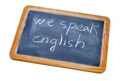 We speak english. Sentence we speak english written with chalk on a blackboard Stock Images