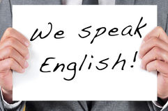 We speak english. A man wearing a suit holding a signboard with the sentence we speak english written in it Stock Photos