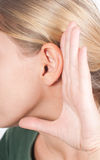Speak louder. Woman holding her hand near the ear, miming the concept of low sounds Royalty Free Stock Photo