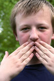 Speak No Evil. Preteen boy with hands covering his mouth stock photography