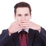 Speak no evil. Business man making the speak no evil gesture over white stock image