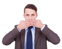 Speak no evil. Business man making the speak no evil gesture over white . young businessman covering his mouth with his hand Stock Photography